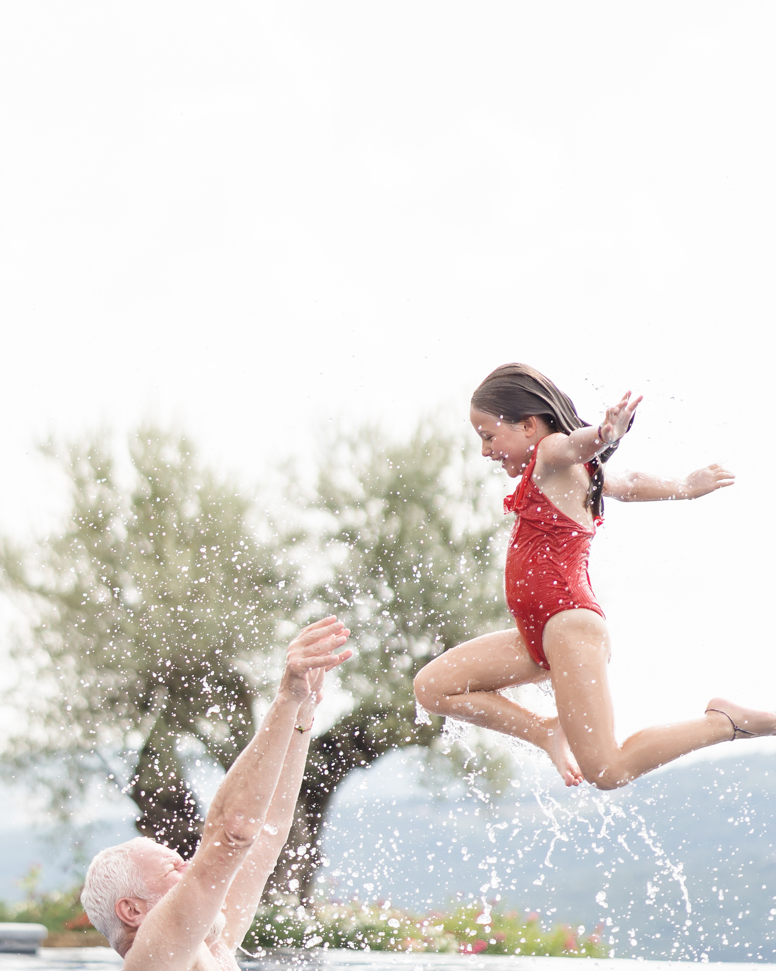 Father playing with his daughter in a swimming pool at Belmond Castello di Casole in Tuscany, Italy