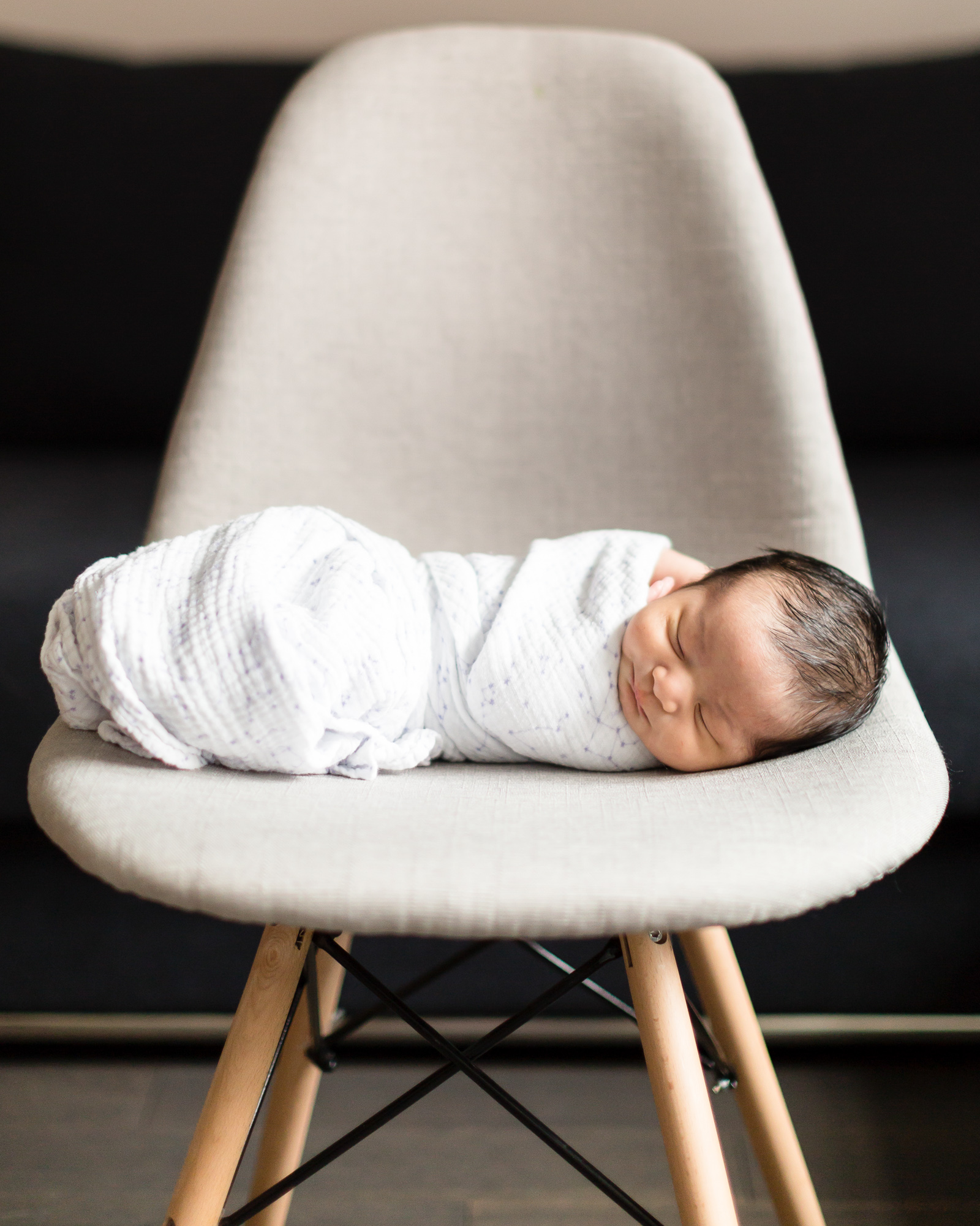 Newborn baby wrapped in a blanket on a chair.