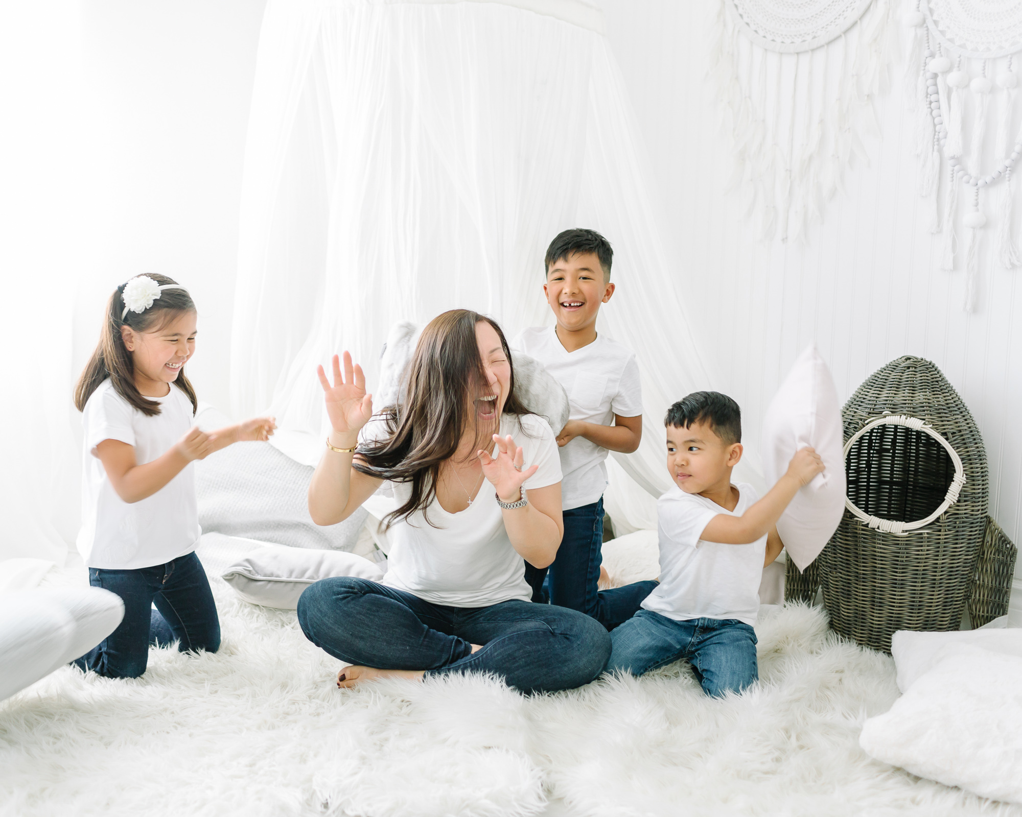 Family photo of a pillow fight with a mother and her kids.
