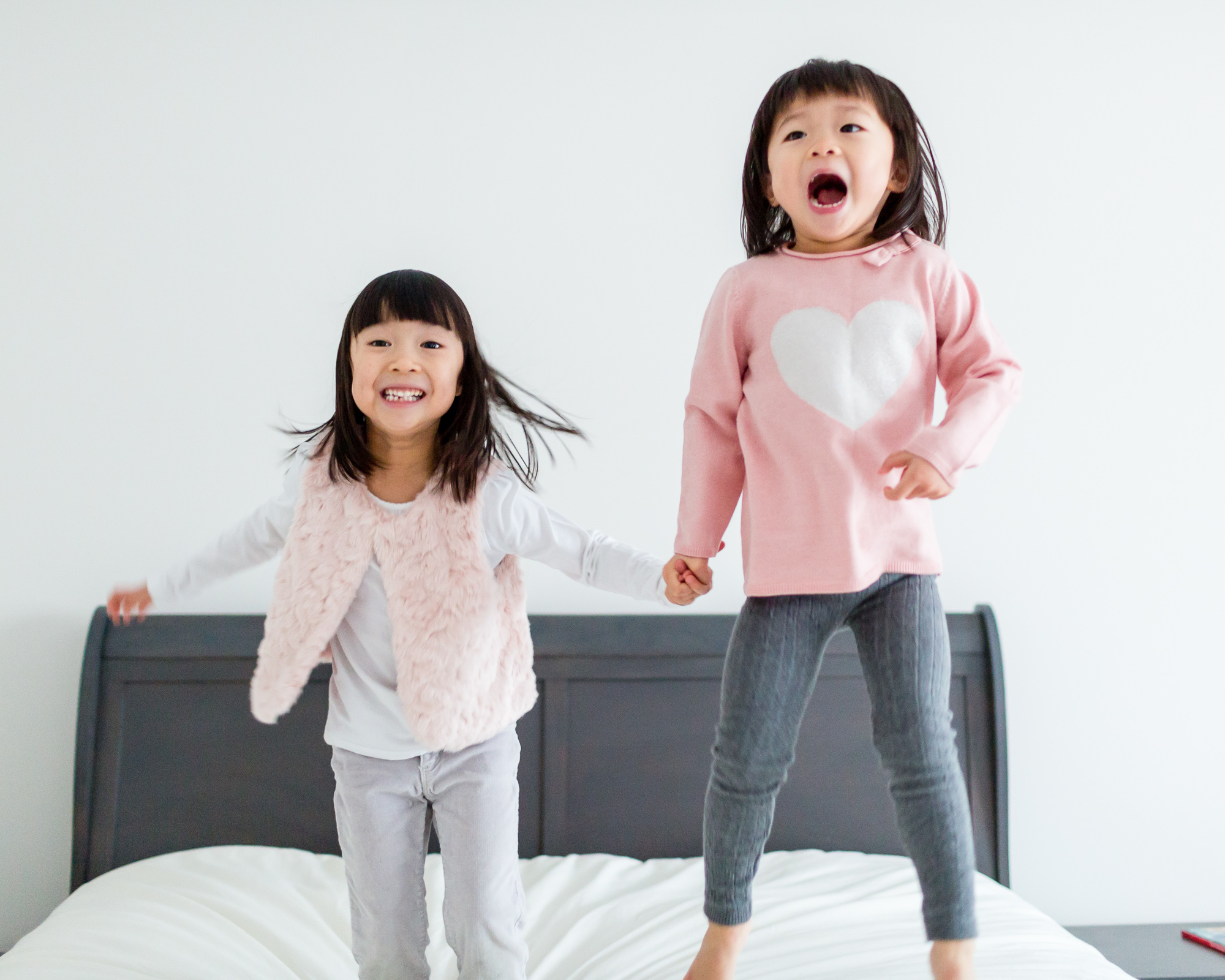 Two sisters jumping on their bed