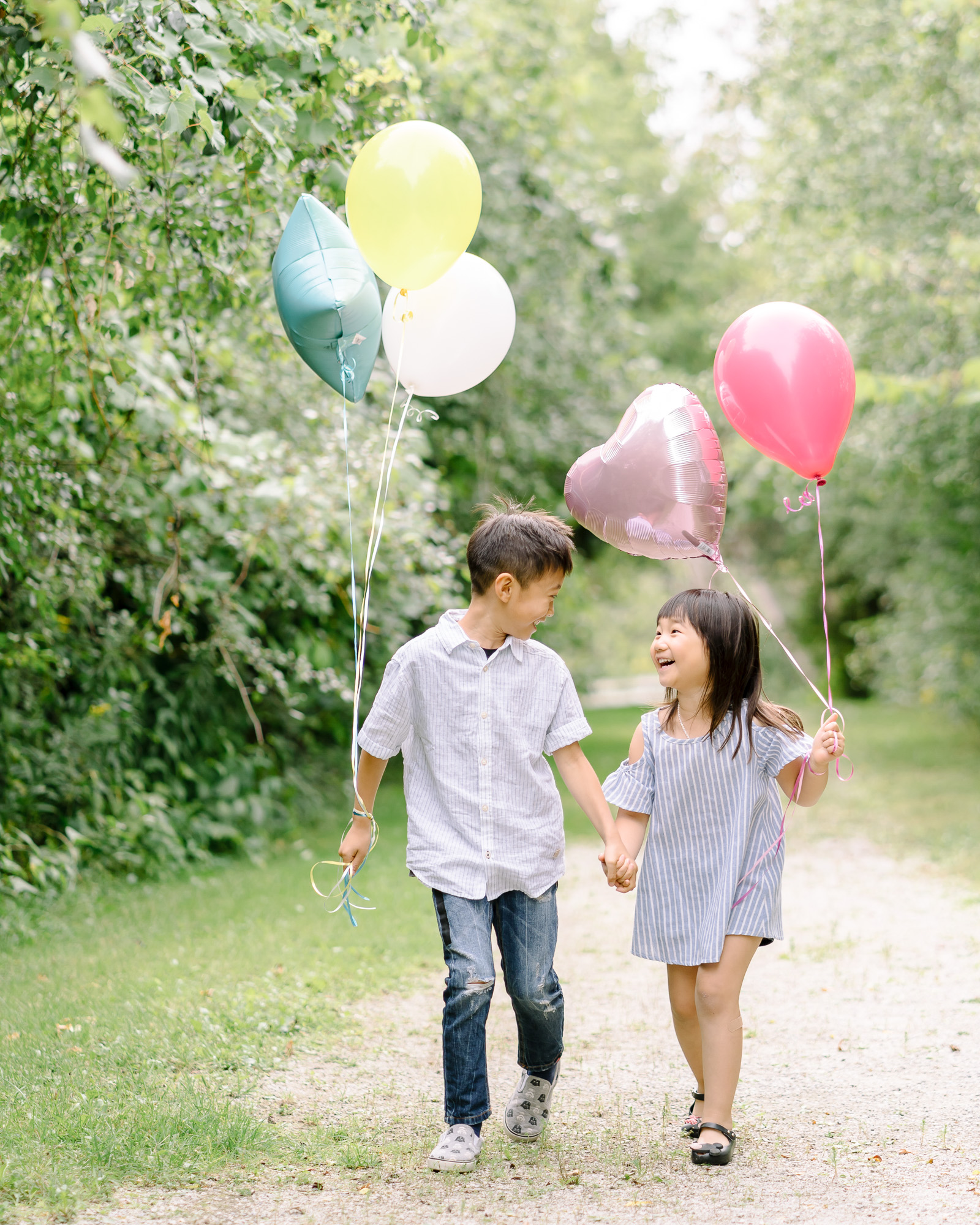 Brother and sister walking with balloons