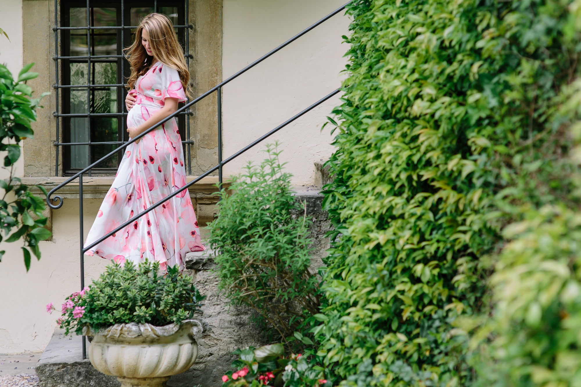 Young pregnant female walking down stairs in a garden in Italy for a maternity session.