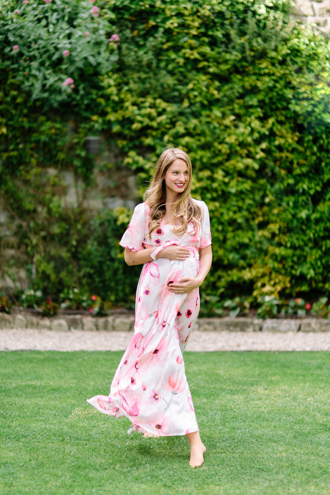 Young pregnant female walking in a garden while holding her pregnant belly in Florence, Italy for a maternity session at Belmond Villa San Michele.