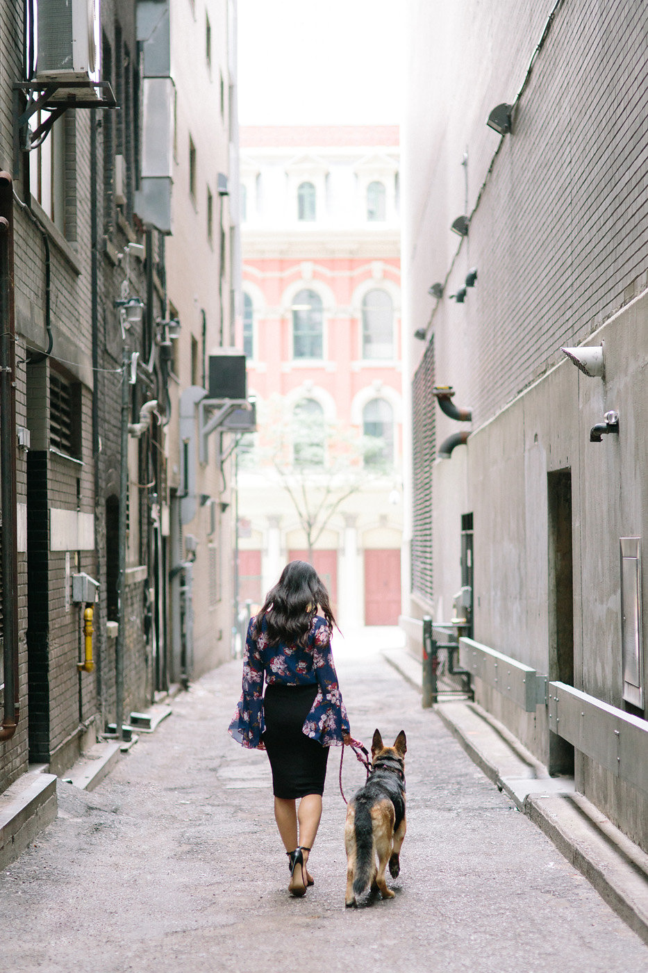 Young Asian female walking away with her German Shepherd dog in downtown Toronto.