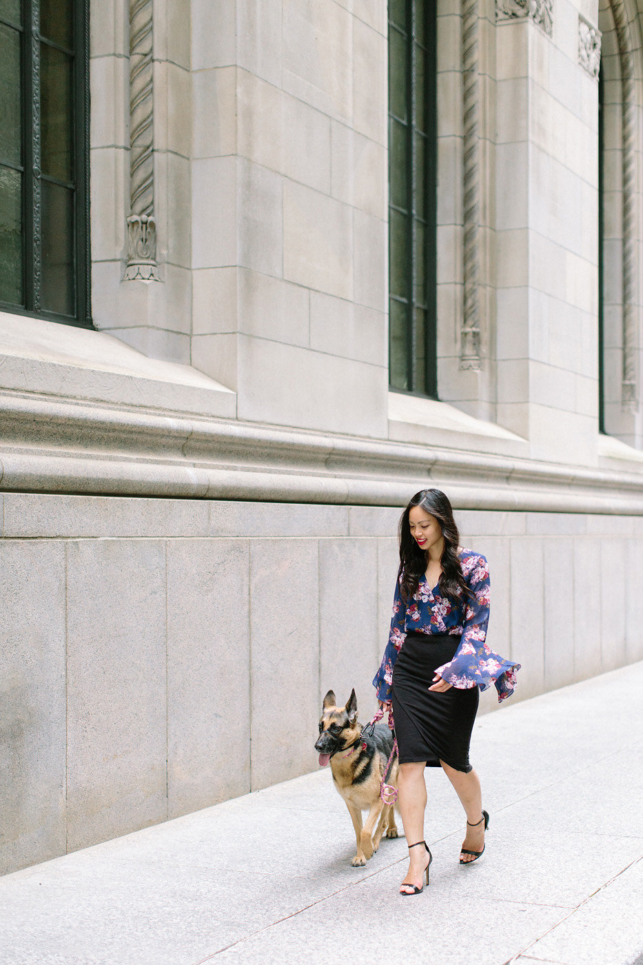 Young Asian female walking with her German Shepherd dog in downtown Toronto.