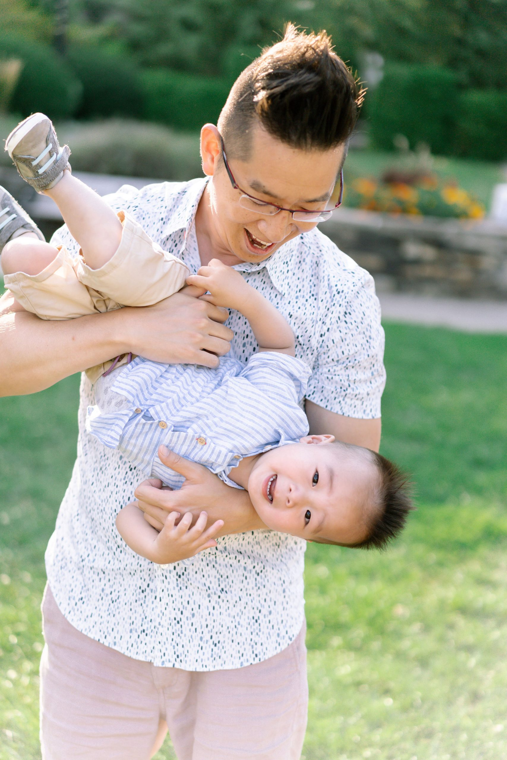 Father holding his son upside while laughing