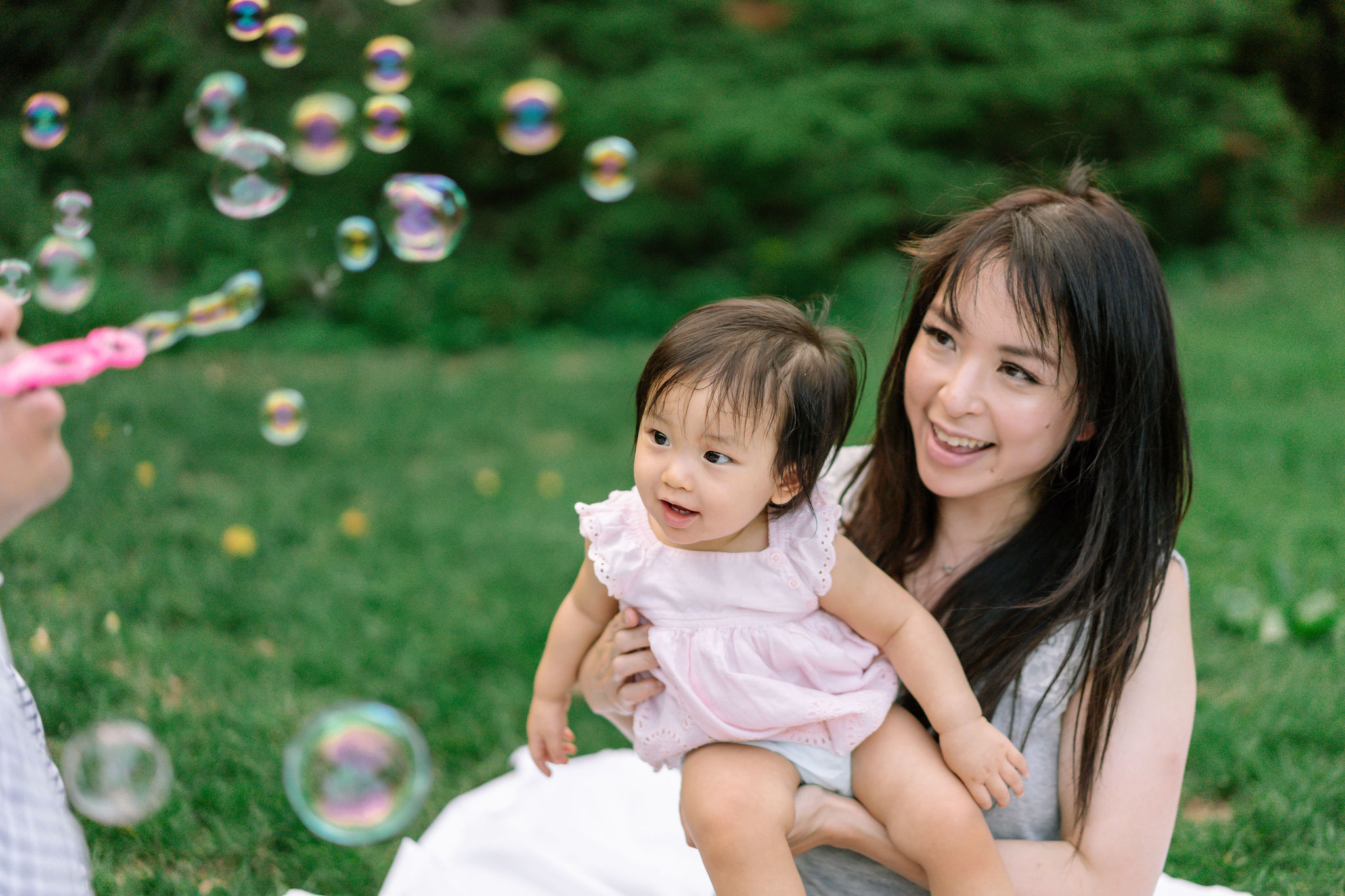 Mother and daughter watching bubbles being blown towards them